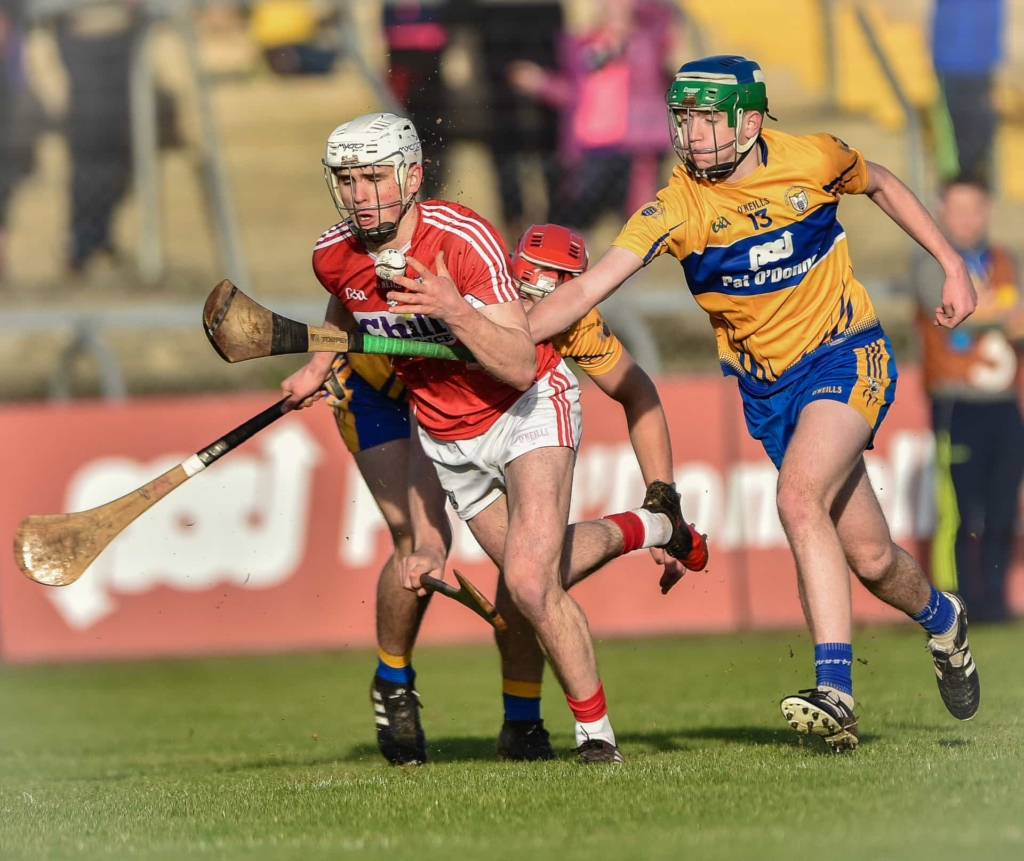 Clare's Billy Connors is beaten in a race for possession by Cork's David Griffin Photo: Martin Connolly